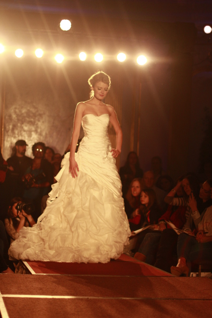 Ian Stuart: Strapless dropped waist ruched taffeta A-line gown with pick up skirt and organza flower detail.